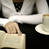 Lectura del libro en cafetería Imagen de archivo libre de regalías