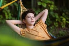 Lectura del muchacho del adolescente en hamaca Imagen de archivo libre de regalías