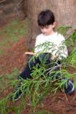 Lectura del muchacho contra un árbol Fotos de archivo libres de regalías