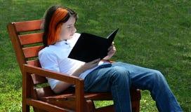 Lectura del muchacho en banco en hierba Fotos de archivo libres de regalías