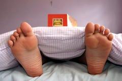 Lectura del muchacho en cama Fotos de archivo