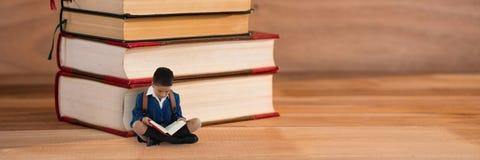 Lectura del muchacho en el piso al lado de una pila de libros Foto de archivo