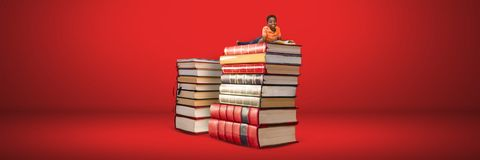 Lectura del muchacho en una pila de libros con el fondo rojo Fotos de archivo libres de regalías