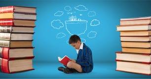 Lectura del muchacho rodeada por la pila de libros y un dibujo con el fondo azul Fotos de archivo libres de regalías