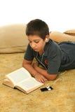 Lectura del muchacho y musi que escucha Foto de archivo