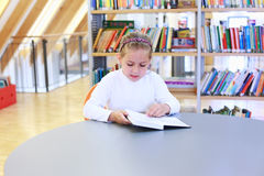 Lectura del niño en biblioteca Fotos de archivo libres de regalías