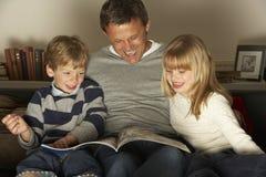 Lectura del padre y de dos niños fotografía de archivo libre de regalías