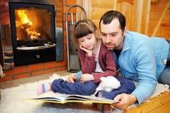 Lectura del padre y de la hija delante de la chimenea imagen de archivo libre de regalías
