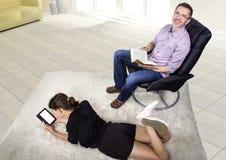 Lectura del padre y de la hija en una sala de estar Foto de archivo