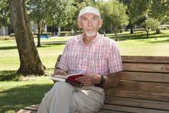 Lectura del viejo hombre al aire libre en campus Fotos de archivo libres de regalías