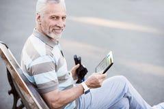 Lectura deportiva del viejo hombre después de la elaboración en el parque Foto de archivo