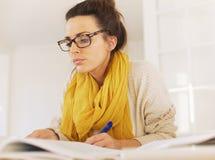 Lectura elegante de la mujer mientras que toma notas Fotografía de archivo libre de regalías