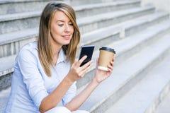 Lectura elegante joven de la mujer profesional usando el teléfono Busin femenino Imagen de archivo libre de regalías