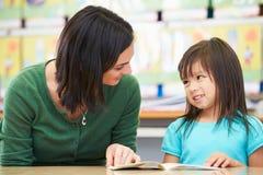 Lectura elemental del alumno con el profesor In Classroom imagen de archivo libre de regalías