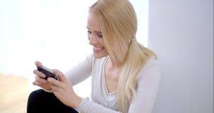 Lectura emocionada de la mujer joven SMS en su móvil