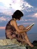 Lectura en la puesta del sol Imagen de archivo libre de regalías