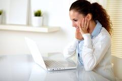 Lectura encantadora de la mujer joven en la pantalla de la computadora portátil Imagenes de archivo