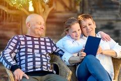 Lectura feliz hermosa del abuela y de abuelo al libro de la nieta en naturaleza en la puesta del sol foto de archivo