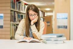 Lectura femenina del estudiante universitario en la biblioteca Fotos de archivo