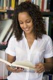 Lectura femenina del estudiante universitario en una biblioteca foto de archivo