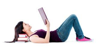 Lectura femenina joven con la pista que se reclina sobre los libros Foto de archivo libre de regalías