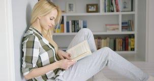 Lectura femenina preciosa en casa Imágenes de archivo libres de regalías