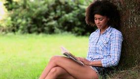 Lectura hermosa de la mujer en el parque que se inclina contra un árbol almacen de metraje de vídeo