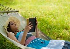 Lectura hermosa de la mujer y relajación en hamaca Fotografía de archivo libre de regalías