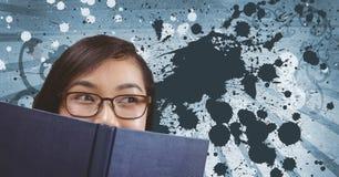 Lectura joven de la mujer del estudiante contra fondo salpicado azul Foto de archivo