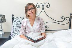 Lectura joven del adolescente en cama Fotos de archivo libres de regalías