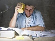 Lectura joven del escritorio del estudiante en casa que estudia en la noche con la pila de libros y de café Imágenes de archivo libres de regalías