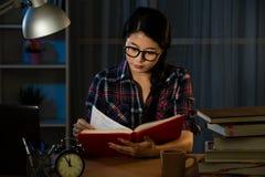 Lectura joven del estudiante que estudia en la noche Fotos de archivo