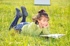 Lectura linda de la muchacha en prado con la tarjeta detrás Imagen de archivo libre de regalías