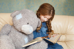 Lectura linda de la niña con el oso de peluche Imágenes de archivo libres de regalías