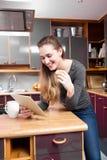 Lectura magnífica sonriente de la mujer joven en tecnología casera relajante Foto de archivo libre de regalías