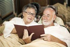 Lectura mayor de los pares en cama Fotos de archivo libres de regalías