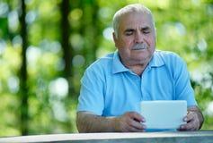Lectura mayor del hombre en una tableta Fotos de archivo libres de regalías
