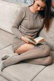 Lectura mientras que se sienta en el sofá Imagen de archivo libre de regalías
