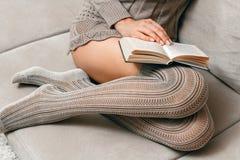Lectura mientras que se sienta en el sofá Fotos de archivo libres de regalías