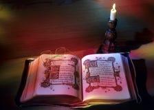 Lectura por la luz de la vela Foto de archivo