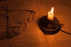 Lectura por luz de una vela Foto de archivo libre de regalías