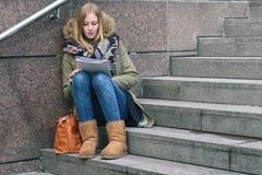 Lectura que se sienta de la mujer joven en pasos urbanos Imágenes de archivo libres de regalías
