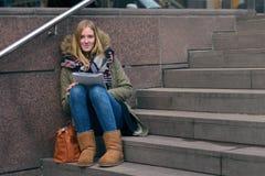 Lectura que se sienta de la mujer joven en pasos urbanos Imagenes de archivo