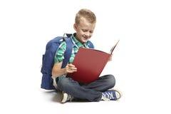 Lectura que se sienta del muchacho de escuela Imágenes de archivo libres de regalías