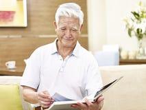 Lectura relajante del hombre asiático mayor un libro en casa Imagen de archivo