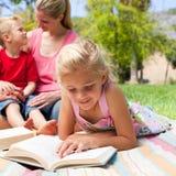 Lectura rubia de la muchacha mientras que teniendo una comida campestre Imagen de archivo libre de regalías
