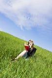 Lectura rubia en hierba Imagen de archivo libre de regalías