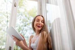 Lectura sonriente de la mujer joven algo en la tableta y la sentada Imagen de archivo