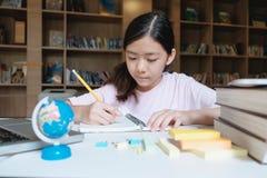 Lectura y escritura de la muchacha en la biblioteca de la escuela Fotos de archivo