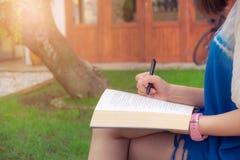 Lectura y marca de la mujer joven algo en el libro que se sienta en jardín Foto de archivo libre de regalías